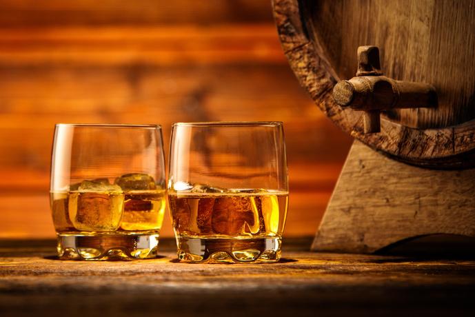 Zwei Gläser Whiskey mit Eis auf einem Holztisch, Holzfaß
