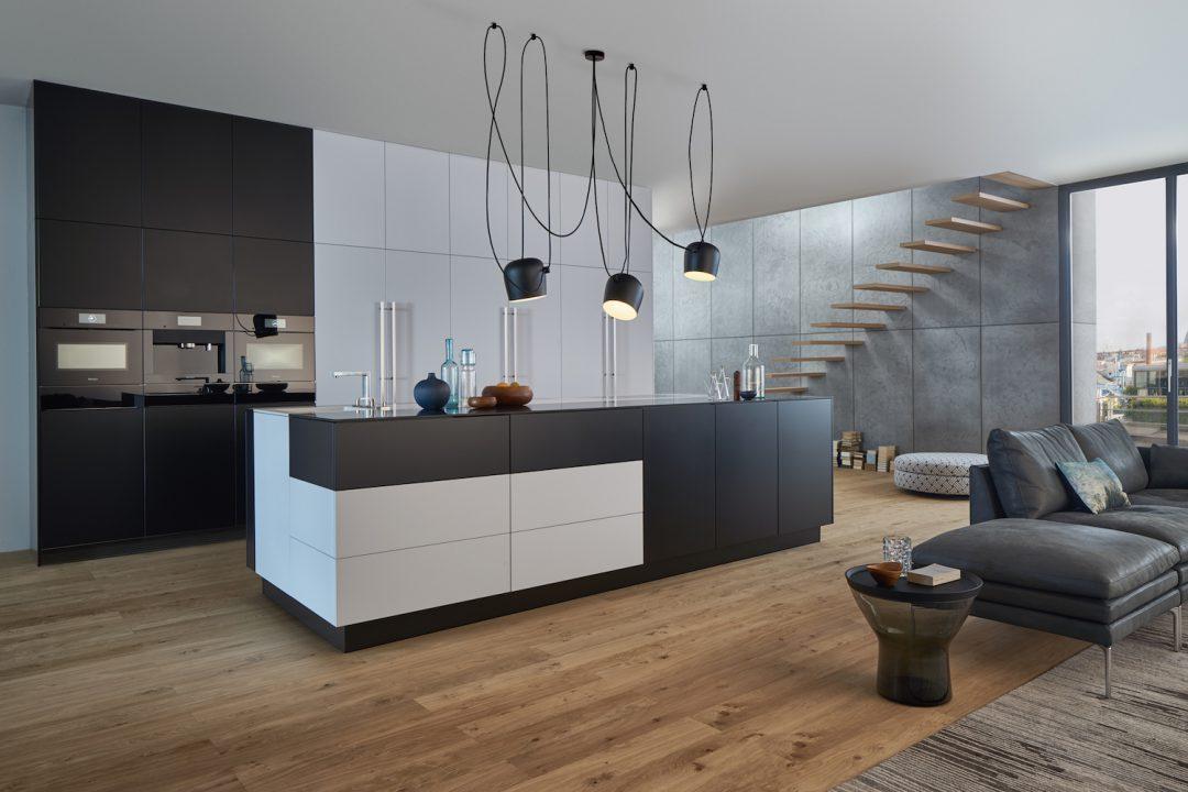 Küchenstudio Bingel&Klein - schwarz weiße Wohnküche - Kücheninsel - Parkettboden - Couch