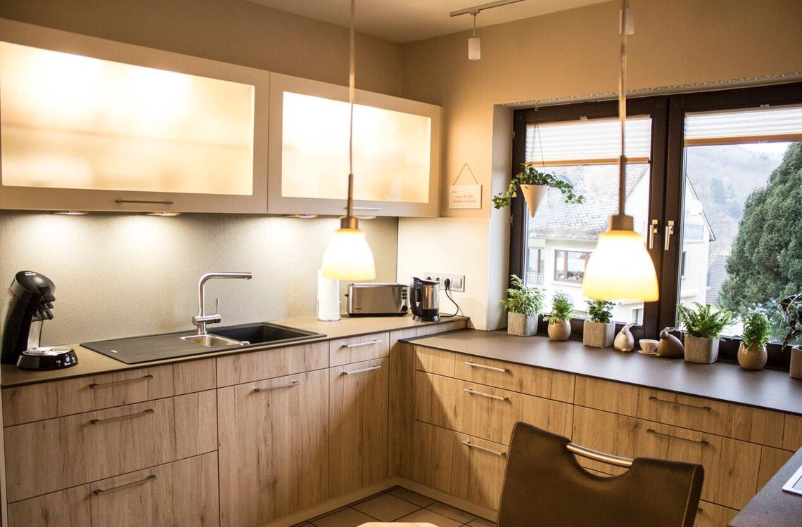 Küchenstudio Bingel - realisierte Küche - Küche Holzdesign -komplette Küche mit Fensterblick - Hängeschränke mit Beleuchtung - cremefarben Pflanzen