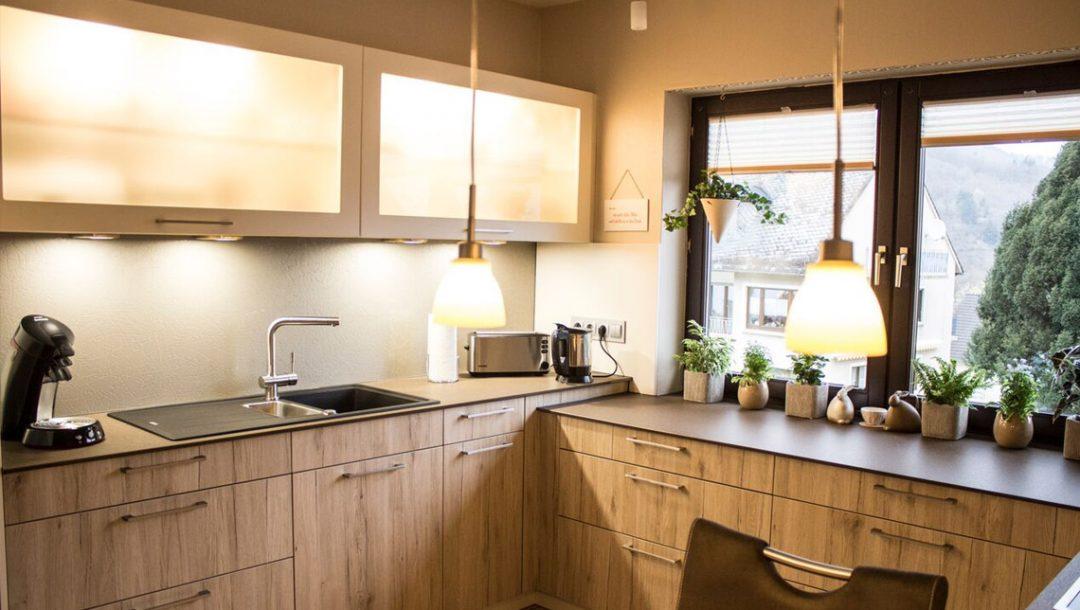 Küchenstudio Bingel - Küche Holzdesign -komplette Küche mit Fensterblick - Hängeschränke mit Beleuchtung - cremefarben Pflanzen