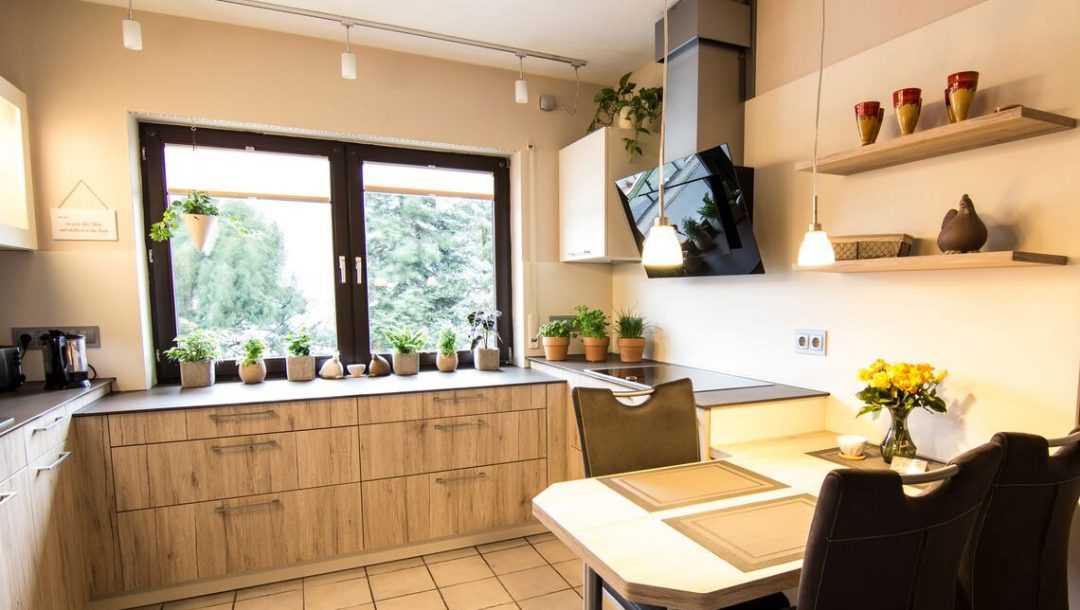 Küchenstudio Bingel - Küche Holzdesign - Küche mit Fensterblick - Esstisch - cremefarben Pflanzen